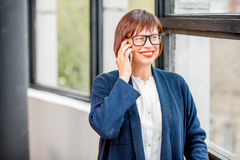Older businesswoman talking phone indoors Stock Images