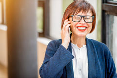 Older businesswoman talking phone indoors Royalty Free Stock Images