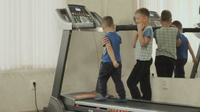 The older child is training the younger to walk on the treadmill. The kid with the trainer trains in the gym near the mirror. The concept of a healthy stock video footage