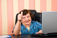 Older corporate woman giving thumbs. Older corporate woman giving  thumbs up and sitting at desktop,check also Business people Stock Images