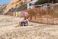Older couple baby boomers sit on beach under umbrella near a chain link fence with dilapidated houses in the background stock image