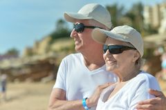 Older couple on beach. Happy older couple in sunglasses on beach Royalty Free Stock Images