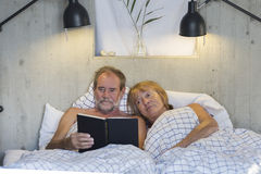 Older couple in bed. Reading a book Royalty Free Stock Photos
