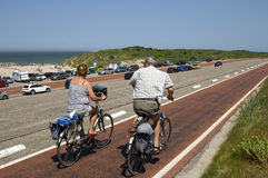 Older couple cycling on Brouwersdam, Netherlands. The Brouwersdam, in the province Zealand,is a construction of the Delta Works, a series of construction Stock Photography