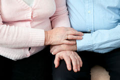 Older Couple Holding Hands. Elderly couple with beautiful hands posing together in  close embrace. Older Couple Holding Hands close up. Elderly couple with Royalty Free Stock Image
