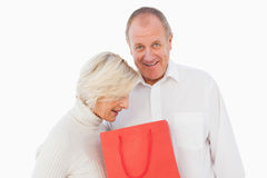 Older couple holding red gift bag Royalty Free Stock Images