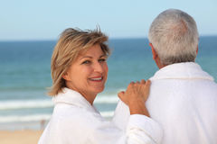 Older couple outdoors in bathrobes. Older couple in bathrobes watching the ocean Stock Photo