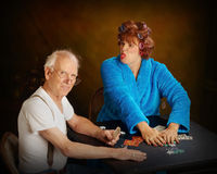 Older couple playing cards. Two senior citizens playing poker Royalty Free Stock Image