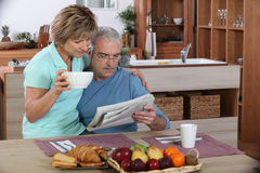 Older couple reading. A newspaper at breakfast Royalty Free Stock Photography