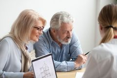 Older couple reading contract at meeting with real estate agent. Considering new home purchase, realtor or bank worker consulting senior family about buying royalty free stock photos