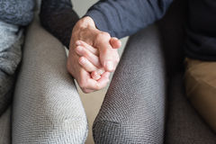 Older couple's hands. Close up of older couple in armchairs holding hands (cropped and selective focus Royalty Free Stock Images
