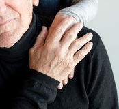 Older couple's hands. Older man's hand covering older woman's hand on his shoulder (cropped Royalty Free Stock Photography