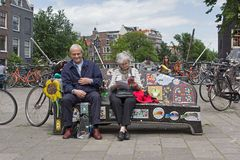 Older couple sitting on bench in Amsterdam Stock Photo