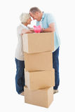 Older couple smiling at each other with moving boxes and piggy bank. On white background royalty free stock images