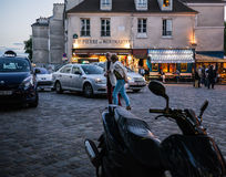 Older couple strolls across Montmartre square between motorcycles and taxis in evening Royalty Free Stock Photography