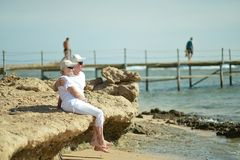 Older couple in sunglasses. Sitting on beach Stock Photo
