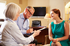 Older Couple Talking To Financial Advisor In Offic. E Filling Out Document Smiling stock photo