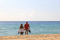 Older couple walking on beach Stock Photos