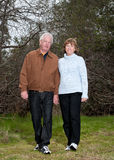 Older couple walking outdoors. In a park setting Royalty Free Stock Photo
