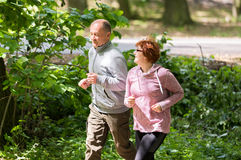 Older couple wearing sportswear and running in forest at mountain royalty free stock photo