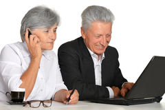 Older couple in the workplace. On a white background Royalty Free Stock Photo