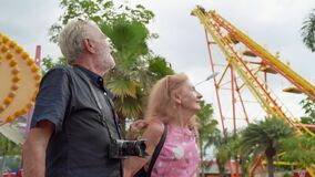 Older couples are visiting amusement parks, they are fun like children. Until forgetting about my own age