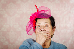 Older cute hispanic woman wearing blue sweater, large pink ribbon on head loking into camera covering her mouth with one Royalty Free Stock Photography