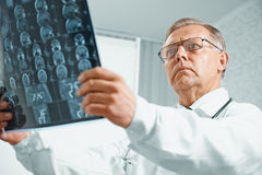 Older doctor examines MRI image Stock Images