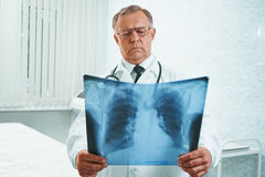 Older doctor examines x-ray image. Older man doctor examines x-ray image of lungs in a hospital stock photos
