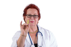 Older Doctor Making a Point with Genuine Friendly Look. Senior Doctor making a point with her green pen , she has a genuine friendly look in her eyes, perhaps Royalty Free Stock Photo
