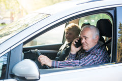 Older driver using smartphone Stock Photography