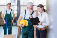 Older employee. Older warehouse employee and his young boss Royalty Free Stock Images