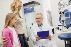 Older eye specialist finished eye examination of child stock images