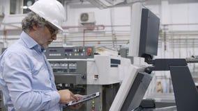Older factory engineer testing industrial machine