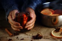 Older female hands holding a glass mug with hot mulled wine next Royalty Free Stock Photography