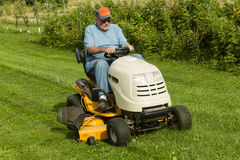 Older Gentleman Cutting Grass On Riding Lawnmower Stock Image