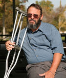 Older gentleman holding crutches. Older gentleman resting on a park bench while holding his crutches and contemplating his accident Royalty Free Stock Photography