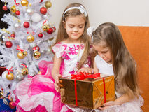 Older girl gives younger unwanted gift Stock Image