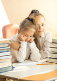 Older girl hugging very upset classmate at classroom Royalty Free Stock Image