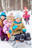 Older girl pushes sled with two little children Royalty Free Stock Photo
