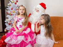The older girl is sitting on lap of Santa Claus and tells poem Stock Images