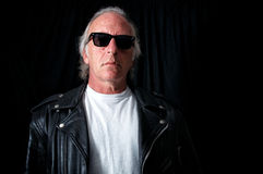Older grey haired biker. Imposing image of older biker against black backdrop looking down at viewer from behind vintage sunglasses. wearing vintage black Stock Photo