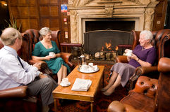 Older group of friends. A group of older senior friends enjoying tea and talking in hotel lounge area Stock Photography