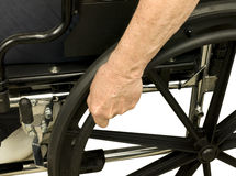 Older hand on wheel chair Stock Images