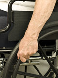 Older hand on wheel chair pushing Stock Images