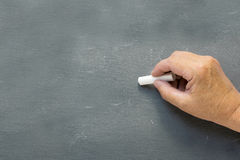 Older hand writes on a blank chalkboard Stock Photo