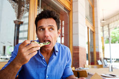 Older handsome man eating pizza at outdoor restaurant. Portrait of an older handsome man eating pizza at outdoor restaurant Stock Photos