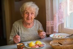 Older  happy woman eating at home at the table. Older woman eating at home at the table Royalty Free Stock Images