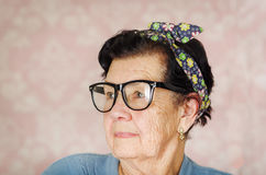 Older hispanic cute woman with flower pattern bow on her head wearing blue sweater and black large framed glasses Royalty Free Stock Photo
