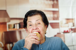 Older hispanic happy woman wearing blue sweater sitting in front of camera having a bite off cupcake Stock Photos